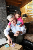 Child and grandfather playing cards — Stock Photo