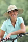 Woman on a bicycle wearing a hat — Stock Photo
