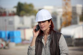 Female architect making a call in construction site — Stock Photo