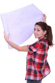 Young woman unrolling wallpaper — Stock Photo