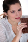Young woman with a huge bar of chocolate — Stock Photo