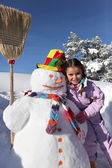 Little girl with snowman — Stock Photo