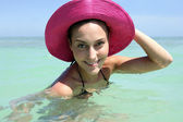 Woman swimming in the sea wearing pink hat — Stock Photo