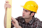 Tradesman checking the quality of his wood — Stock Photo