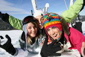 Three friends laying in the snow with ski equipment — Stock Photo
