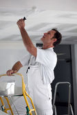 Painter using roller to coat ceiling — Stock Photo