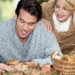 Couple with basket full of mushrooms and chestnuts - Stock Photo