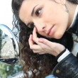 Woman looking her eye in the rearview mirror - Stock Photo