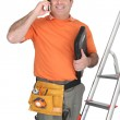 Man on cellphone with ladder and plumbing tools — Stock Photo #10891686