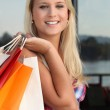 Blonde girl with bags — Stock Photo