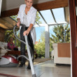 Foto Stock: Young woman vacuuming