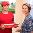 Young man delivering pizza — Stockfoto