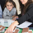 Female architect in office with little girl pointing at model — Stock Photo
