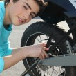 Teenage boy repairing motorcycle — Stock Photo #10893715