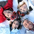 Friends lying in the snow — Stockfoto