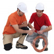 Two plumbers with copper pipe — Stock Photo
