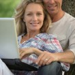 Happy couple outdoors with laptop — Stock Photo #10896685