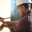 Construction worker marking wooden frame — Stock Photo #10896934