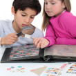Stock Photo: Two kids collecting stamps.