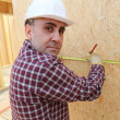 Stock Photo: Builder measuring a wall