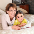 Stock Photo: Mother and daughter reading together on bed