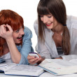 Two girlfriends studying and having fun together - Stock Photo