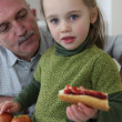 Little girl with grandfather eating sandwich — Stock Photo