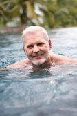 Elderly man swimming — Stock Photo