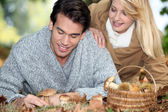 Couple with basket full of mushrooms and chestnuts — Stock Photo