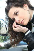 Woman looking her eye in the rearview mirror — Stock Photo