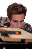 Carpenter checking plank of wood — Stock Photo