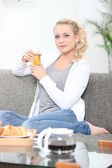 Woman having breakfast in her living room — Stock Photo