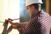Construction worker marking wooden frame — Stock Photo