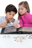 Two kids collecting stamps. — Stock Photo