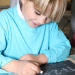 Little boy writing on a slate - Stock Photo