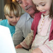 Grandfather and grandchildren with laptop — Stock Photo