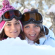 Two young women playing in the snow — Stock Photo