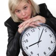 Blond businesswoman leaning on large clock — Foto de Stock
