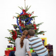 Couple sitting in front of a Christmas tree — Stock Photo