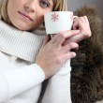 Woman sitting on cosy sofa with mug of coffee — Stock Photo