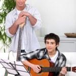 Man teaching teenage boy the guitar — Stock Photo #10904337