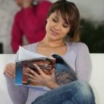 Woman reading a magazine on a sofa — Stock Photo