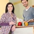 Couple reading recipe in the kitchen — Stock Photo