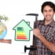 Craftsman holding an energy consumption label and a globe with green plant on it — Stock Photo #10906361