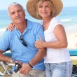 Middle-aged couple enjoying bike ride by the sea — Stock Photo #10906380