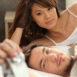 Asian beauty with boyfriend in bed — Stock Photo
