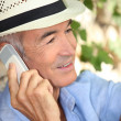 Royalty-Free Stock Photo: Man wearing a straw hat and talking on his mobile phone