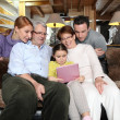 Family gathering at home with laptop — Stock Photo