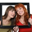 Two girls behind black frame — Stok fotoğraf