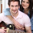 Couple sat on the couch with electric guitar — Stock Photo